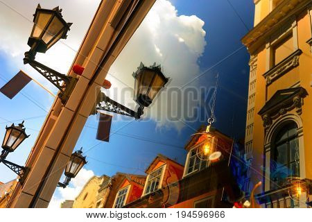 Reflection of the blue sky and facades of old houses with street lights in a summer sunny day. Riga