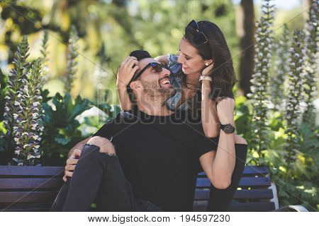 Happy Couple Sitting On Bench Looking At Each Other