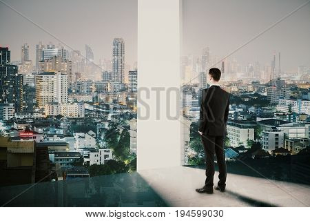 Side view of young businessman looking at bright gap in abstract room interior with night city view. Search concept. Double exposure