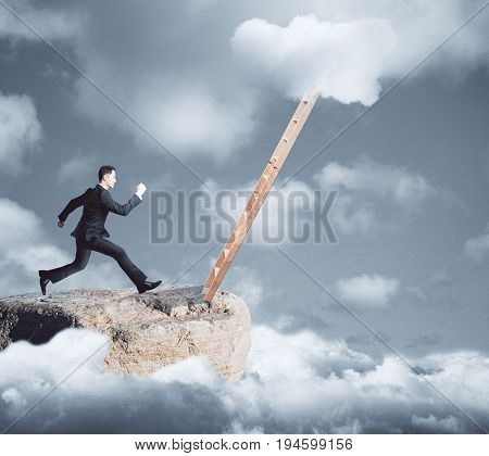 Side view of young businessman on mountain top running towards ladder on dull sky background. Growth concept