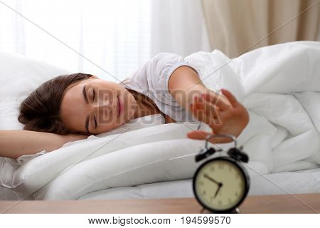 Sleepy young woman stretching hand to ringing alarm willing turn it off. Early wake up, not getting enough sleep, getting work concept