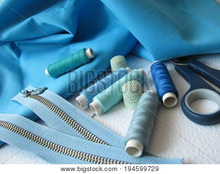Sewing utensils with twisted thread, zipper and buttons