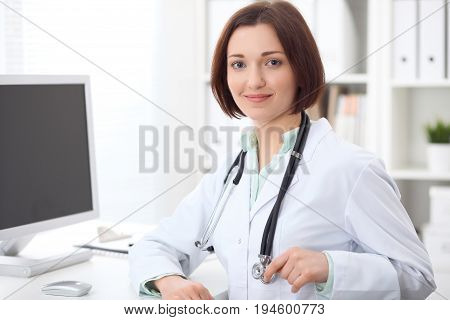 Young brunette female doctor sitting at a desk and working on the computer at the hospital office.  Health care, insurance and help concept. Physician ready to examine patient