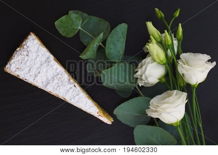Classic French white praline layer cake decorate by white flowers on black slate stone plate
