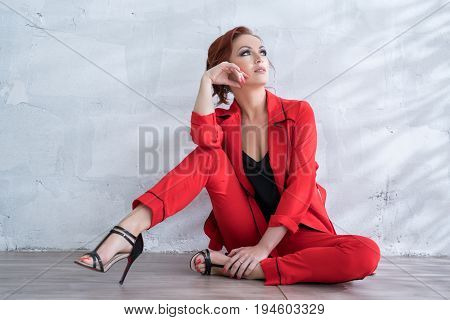 Beautiful red haired woman in nice red pantsuit sitting on floor with a dreamy look studio portrait