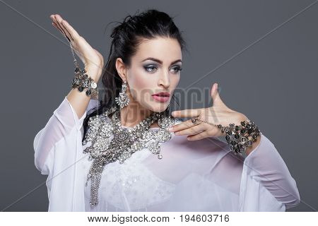 Young woman belly dancing on grey background