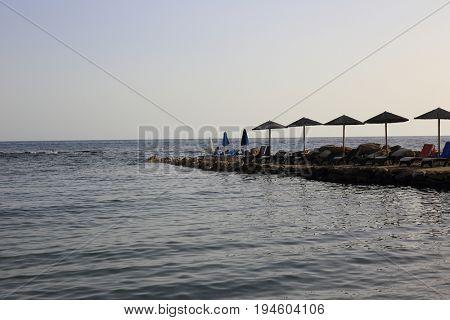 Sunbeds on beach on sunny day in summer on Greek island.