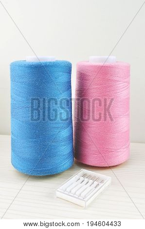 spools of thread of blue and pink and pack of needles for sewing machines