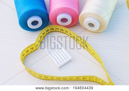 spools of sewing thread, blue, pink, beige, pack of needles for sewing machines and tailor's meter heart