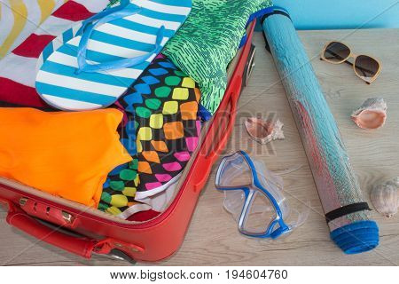 Anticipation of voyage. Women's clothes and accessories in black suitcase. Open suitcase packed for travelling