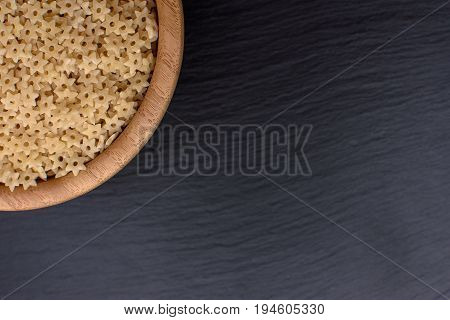 Pasta In The Form Of Asterisks Lie In A Wooden Cup On A Black Stone Board, Space For Text