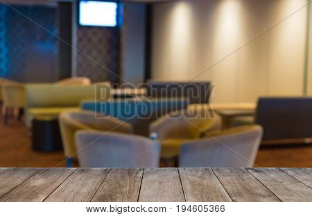 Empty Wooden Table In Front Of Hotel Waiting Area With Armchairs, Blurred Background With Selective