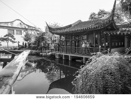 Suzhou, China - Nov 5, 2016: A tranquil traditional Chinese architectural scene, featuring pavilion, landscaped trees, rockery, pond and bush. Monochrome image.