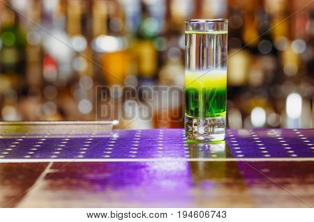 A green Mexican cocktail on the bar. In the background a blurred background bar. night life. Horizontal photo