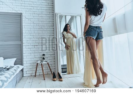 Fits perfectly! Rear view of attractive young woman trying on her dress while looking in the mirror at home