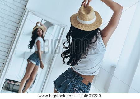 Ready to vacation. Rear view of attractive young woman trying on her sun hat and smiling while looking in the mirror at home