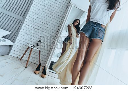 Perfect dress. Close up rear view of attractive young woman trying on her dress and smiling while looking in the mirror at home