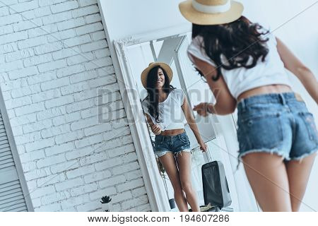 Ready for summer adventures. Rear view of attractive young woman trying on her sun hat and smiling while looking in the mirror at home