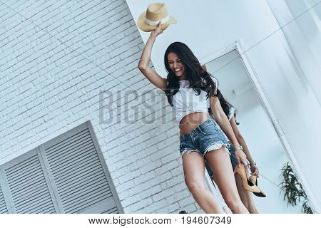 She is all about style. Attractive young woman holding a sun hat beyond her head and smiling while standing at home