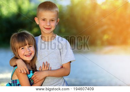 Two little children brother and sister together. Girl in dress hugging boy. Family relations concept.