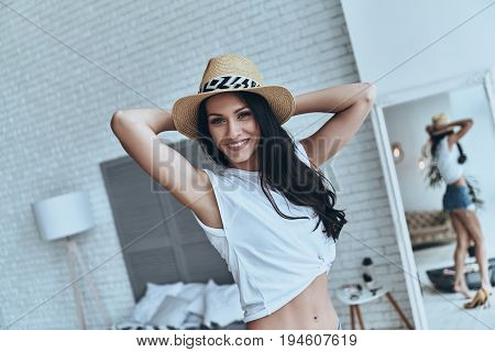 Ready foe vacation. Attractive young woman keeping hands behind head and smiling while standing in the bedroom at home