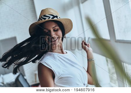 Irresistible girl. Attractive young woman keeping eyes closed and smiling while standing in the bedroom at home