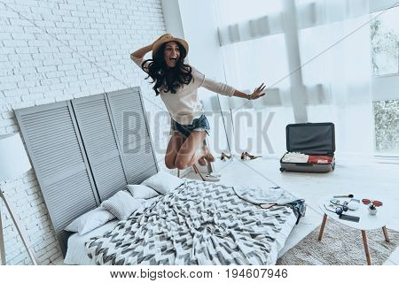 Beauty in the mid-air. Full length of playful young woman in sun hat smiling while jumping on the bed