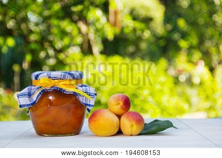 Homemade jam on a green natural background. A jar of home apricot jam and fresh apricots on a white table.