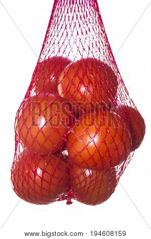 Packaged tomatoes hanging in red plastic net. Isolated over white background