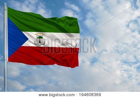 National flag of Equatorial Guinea on a flagpole in front of blue sky.