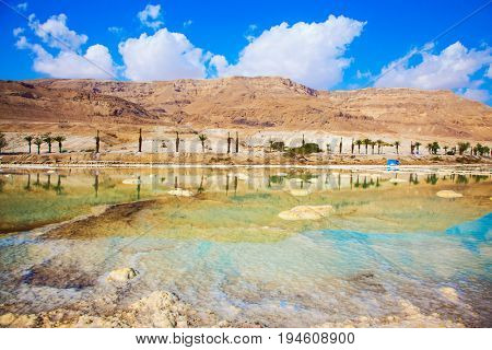 Hot day at the seaside resort on the Dead Sea. The evaporated salt has developed into fantastic patterns. The concept of medical and ecological tourism