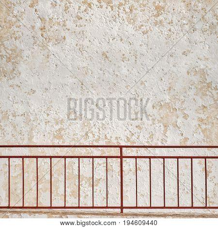 metal grunge railings near the cracked stucco wall