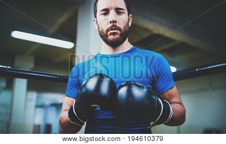 Young man in boxing gloves. Young Boxer fighter over blurred background.Boxing man ready to fight. Boxing, workout, muscle, strength, power - the concept of strength training.Horizontal