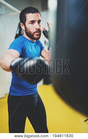 Concept of a healthy lifestyle.Young athlete fighter practicing kicks with punching bag.Kick boxer boxing as exercise for the fight.Boxer man hits punching bag.Vertical