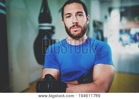 Muscular strong boxer in gloves standing with arms crossed near punching bag in fitness gym on blurred background.Young caucasian boxer in black gloves.Horizontal