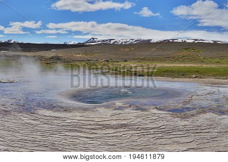 Hot steam coming from the boiling water in the central Iceland in the geothermal area of Hveravellir as a symbol of powerful geothermal green energy