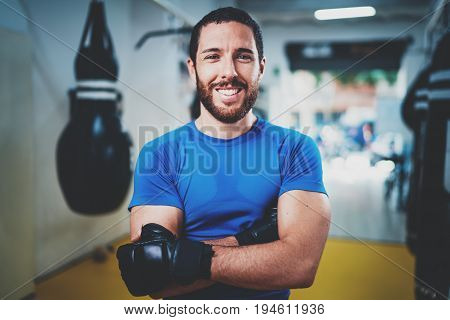 Muscular smiling boxer in gloves standing with arms crossed near punching bag in fitness gym on blurred background.Young caucasian boxer in black gloves.Horizontal