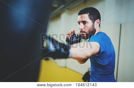 Concept of a healthy lifestyle.Bearded muscular man fighter practicing kicks with punching black bag.Kick boxer boxing as exercise for the fight.Boxer hits punching bag in gym.Horizontal