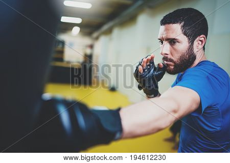 Concept of a healthy lifestyle.Hispanic muscular man fighter practicing kicks with punching black bag.Kick boxer boxing as exercise for the fight.Boxer hits punching bag in gym.Horizontal
