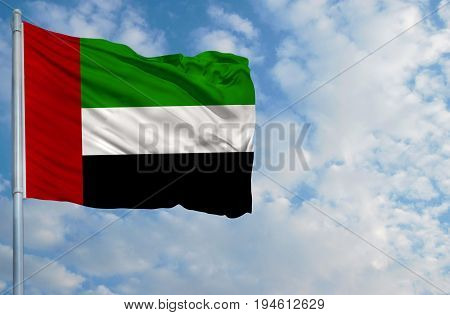 National flag of United Arab Emirates on a flagpole in front of blue sky.