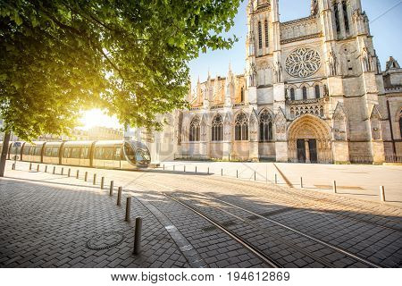 Morning view on the beautiful saint Pierre cathedral with modern tram in Bordeaux city, France