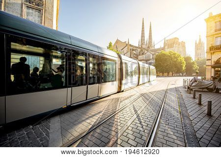 Morning street view with tram and saint Pierre cathedral in Bordeaux city, France
