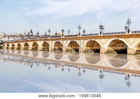 View on the famous saint Pierre bridge with reflection on the water in Bordeaux city, France