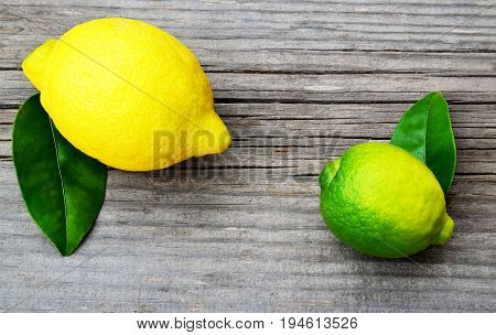 Fresh ripe organic lemon and lime fruits on old wooden table.Lemon and lime.Diet or aromatherapy concept.Copy space,selective focus.