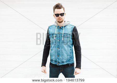 Handsome Hipster Guy With Sunglasses And A Stylish Denim Jacket Near A White Wooden Wall