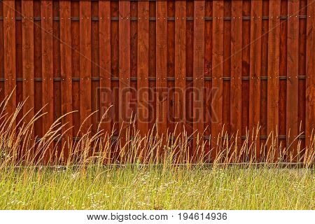 Brown background of wooden fence boards and grass