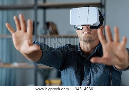 Seems real. Passionate admirable handsome man longing for new experiences and using special device for exploring virtual reality