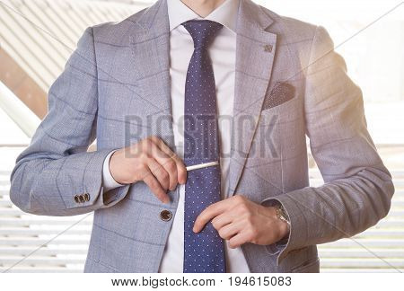 Unrecognizable businessman setting the tie straight by adjusting his tie pin.