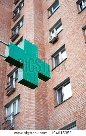 Pharmacy sign on the street. Green pharmacy cross on a background of the building.