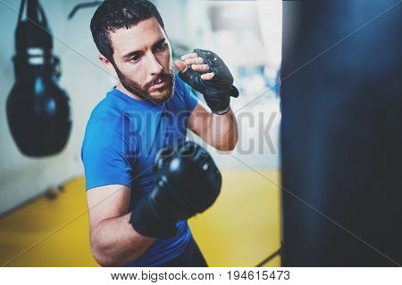 Young boxer doing some training on punching bag at gym. Bearded caucasian boxer training with punching bag in gym.Concept of a healthy lifestyle.Horizontal